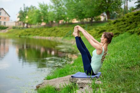 A young sports girl practices yoga on a green lawn by the river, assans posture. Unity with nature