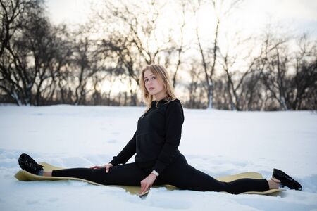 Young caucasian female blonde in leggings stretching exercise sitting on a string at open air in snowy forest. fit and sports lifestyle. Stock Photo
