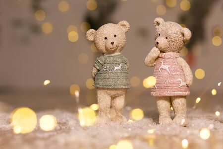 Decorative figurines of a Christmas theme. Figurines of cute teddy bears of a boy and a girl in sweaters with deers. Festive decor, warm bokeh lights 写真素材