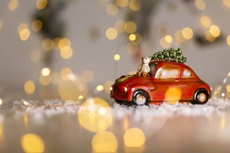 Decorative figurines of a Christmas theme. A statuette of a red car on which a teddy bear sits. Christmas tree decoration. Festive decor, warm bokeh lights 写真素材