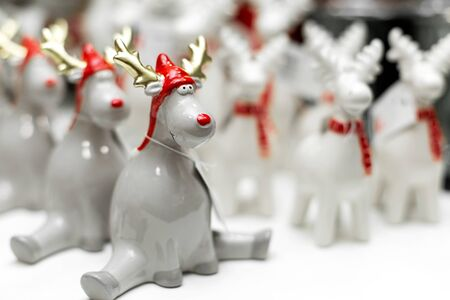 Decorative Christmas-themed figurines. A set of statues of strange Christmas deers are sitting in a twine. Christmas tree decoration. Festive decor.