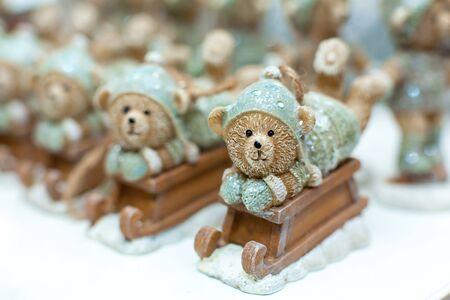 Decorative figurines of a Christmas theme. Statuette of a teddy bear on a wooden sleigh. Christmas tree decoration. Festive decor, warm bokeh lights