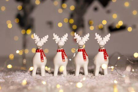 Decorative Christmas-themed figurines. Christmas deer. Christmas tree decoration. Festive decor, warm bokeh lights