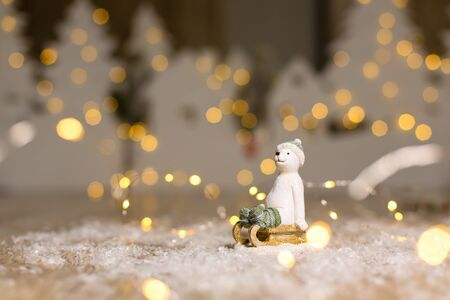 Decorative Christmas-themed figurines. The statuette of a polar bear sits on a wooden sled, in a knitted hat and socks. Christmas tree decoration. Festive decor, warm bokeh lights 写真素材