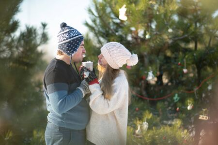 The guy with the girl walk and kiss in the winter forest with a mug of hot drink. A cozy winter walk through the woods with a hot drink. Loving couple, winter holidays.