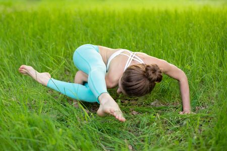 A young sports girl practices yoga in a quit green summer forest, yoga assans posture. Meditation and unity with nature.