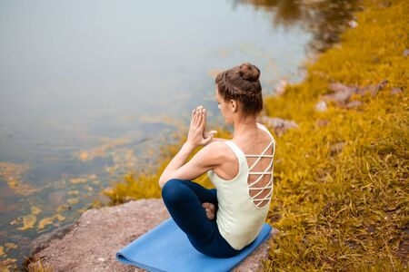A young sports girl practices yoga on a fall yellow lawn by the river, use yoga assans posture. Meditation and unity with nature.