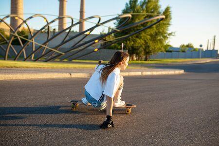 stylish girl in white stockings ride on longboard.