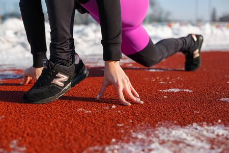 Close-up girl in sportswear on the track for running on a snow-covered stadium is preparing to jog. running from a low start to a snowy stadium. Fit and sport lifestyle.