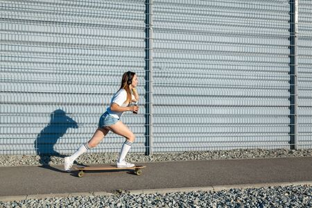 stylish girl in white stockings ride on longboard down the street and listening music. Space for text.