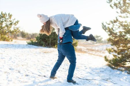 Loving couple play in the winter in the forest. The guy threw the girl on his back and runs with her through the forest. Laugh and have a good time