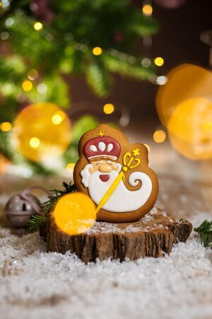 Holiday traditional food bakery. Gingerbread old kindly wizard in cozy decoration with garland lights and cup of hot coffee.