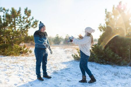 Loving couple play snowballs in winter in the forest. Throw each other snow. Laugh and have a good time. Imagens