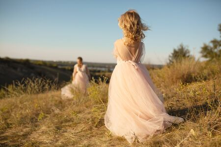 A little girl in a pink princess dress goes to meet her mom. Imagens