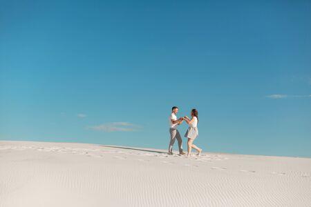 Romantic couple in love running on white sand in desert