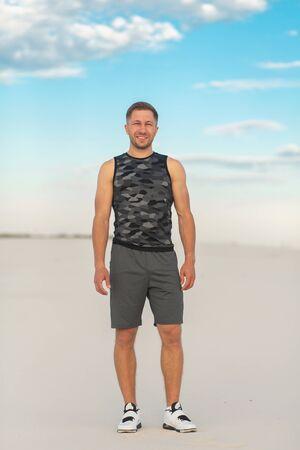 Fitness man doing exercises in sand desert. Sport concept
