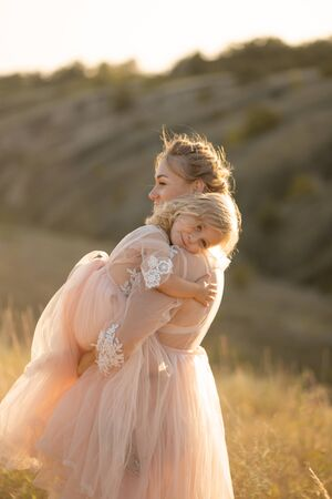 A young family in nature in identical dresses. beautiful young mom holds her daughter in her arms. Field and hills background.