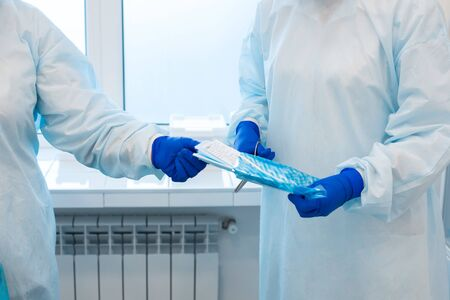 A nurse opens a bag with a sterile disposable instrument before surgery. 写真素材