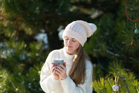 Girl drinks a hot drink with marshmallows in the winter in the forest. Cozy winter walk through the woods with a hot drink. Imagens