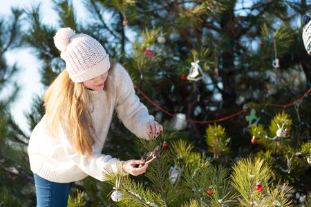 girl decorates with a decorative toys and garlands a green New Year tree on the street in winter in the forest. Christmas tree decorations.
