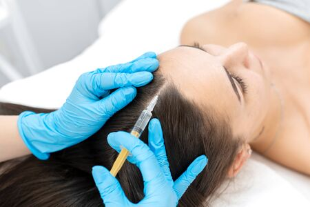 Close-up, the beautician makes injections of vitamins into the scalp for strengthening the hair Imagens