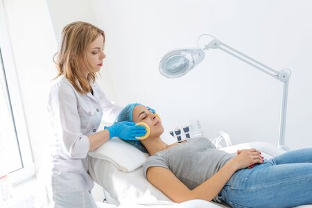 A woman, a professional doctor, a beautician cleanses the patients face with sponges before applying the mask for skin care.