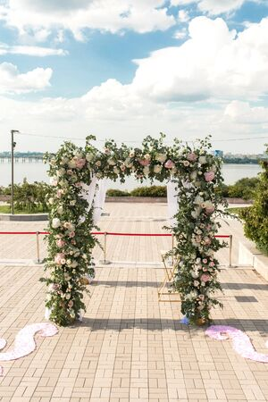 A festive chuppah decorated with fresh beautiful flowers for an outdoor wedding ceremony.