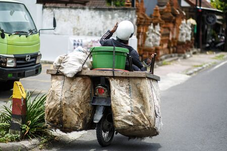 Asian biker trader rides a motorcycle on a road to which huge bags of groceries are tied
