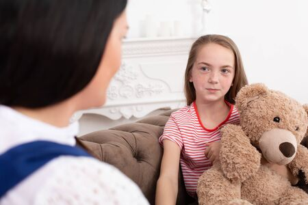 A woman is a professional child psychologist talking with a teenage girl in her cozy office. Psychological assistance to children. Teen girl hugs a teddy bear. Imagens