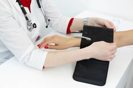 Physiotherapist puts on a medical tonometer to measure pressure on the patients arm. Imagens