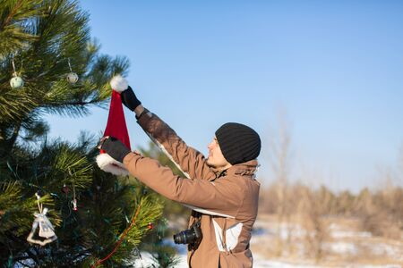 the guy decorates with a decorative toy and garland a green Christmas tree on the street in the winter in the forest. Christmas tree decorations.