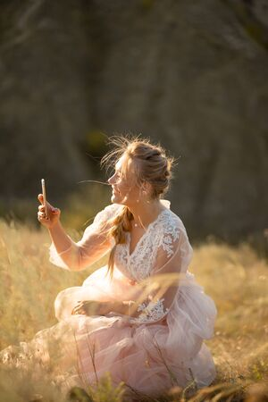 Beautiful girl in a pink dress takes a photo on a cell phone sitting in a field.
