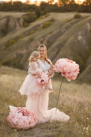 Mom with daughter in pink fairy-tale dresses walk in nature. The childhood of the little princess. Large pink decorative flowers.