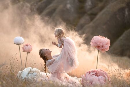 Mom and daughter in pink fairy-tale dresses play in a field surrounded by Big pink decorative flowers.