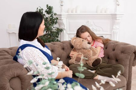 A woman is a professional child psychologist talking with a teenage girl in her cozy office. Psychological assistance to children. Teen girl embarrassed and hiding behind a teddy bear.