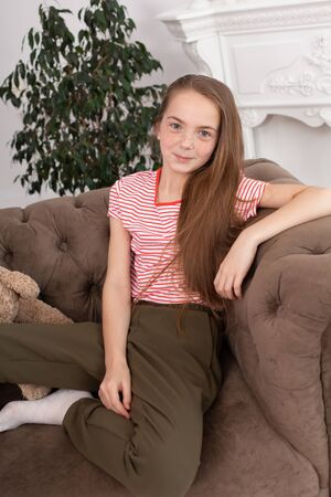 teenage girl with freckles sit on her favorite cozy sofa. Imagens