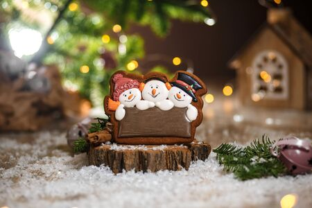Holiday traditional food bakery. Gingerbread three fun snowmans in cozy warm decoration with garland lights.