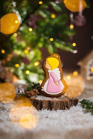 Holiday traditional food bakery. Gingerbread cute angel girl in cozy warm decoration with garland lights.