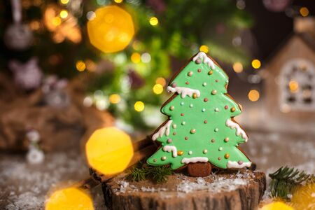 Holiday traditional food bakery. Gingerbread green christmas tree in cozy warm decoration with garland lights.