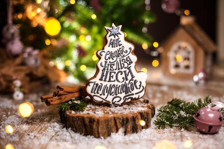 Holiday traditional food bakery. Gingerbread white christmas tree in cozy warm decoration with garland lights.