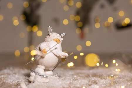 Decorative Christmas-themed figurines. A white gnome statuette with a white beard is skiing. Christmas tree decoration. Festive decor, warm bokeh lights Archivio Fotografico