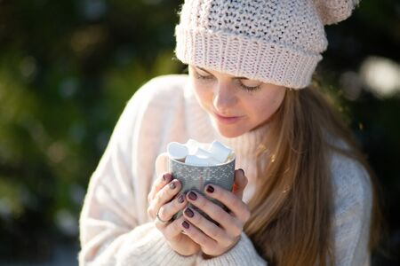 Girl drinks a hot drink with marshmallows in the winter in the forest. A cozy winter walk through the woods with a hot drink. Close-up holding a mug.