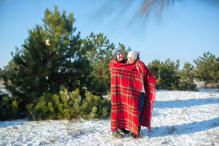 walking in the winter in the woods a guy wraps his girlfriend in a warm red checkered plaid so that she warms herself.