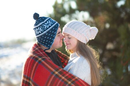 Winter walk through the woods. The guy with the girl kissed wrapped in a red checkered plaid. Imagens