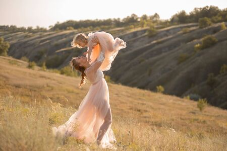 A girl in a pink airy dress holds a little girl in her arms. Sunset, summer. Field and hills. Imagens