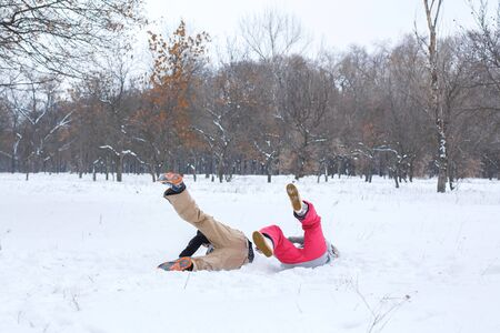 Loving couple having fun, laughing, playing and throwing snowballs in a winter park. A boyfriend  and a girl friend spend winter time together