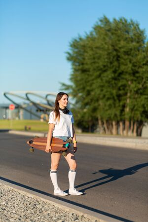 stylish girl in white stockings walking with longboard. Imagens