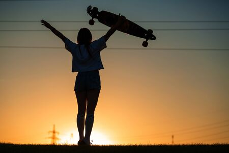 girl looks at sunset holding a longboard in her hand. Imagens