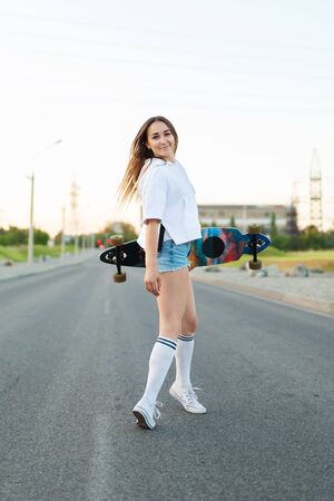 Beautiful sexy young girl in short shorts walking with longboard in sunny weather. Leisure. Healthy lifestyle. Extreme sports. Fashion look, outdoor hipster portrait, Bali, sneakers,hipster,sunse. 版權商用圖片
