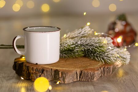 Decoration for New Years holidays. Warm cozy atmosphere. White metal mug on a wooden stand, next to a snowy Christmas tree branch